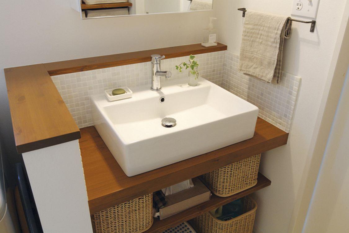 木製カウンターにスクエア型の洗面ボウルを置き、モザイクタイルを組み合わせた洗面台