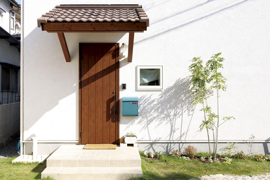 白い壁に芝や植栽の緑が良く映える玄関。小窓から覗くカーテンや水色のポストもお洒落