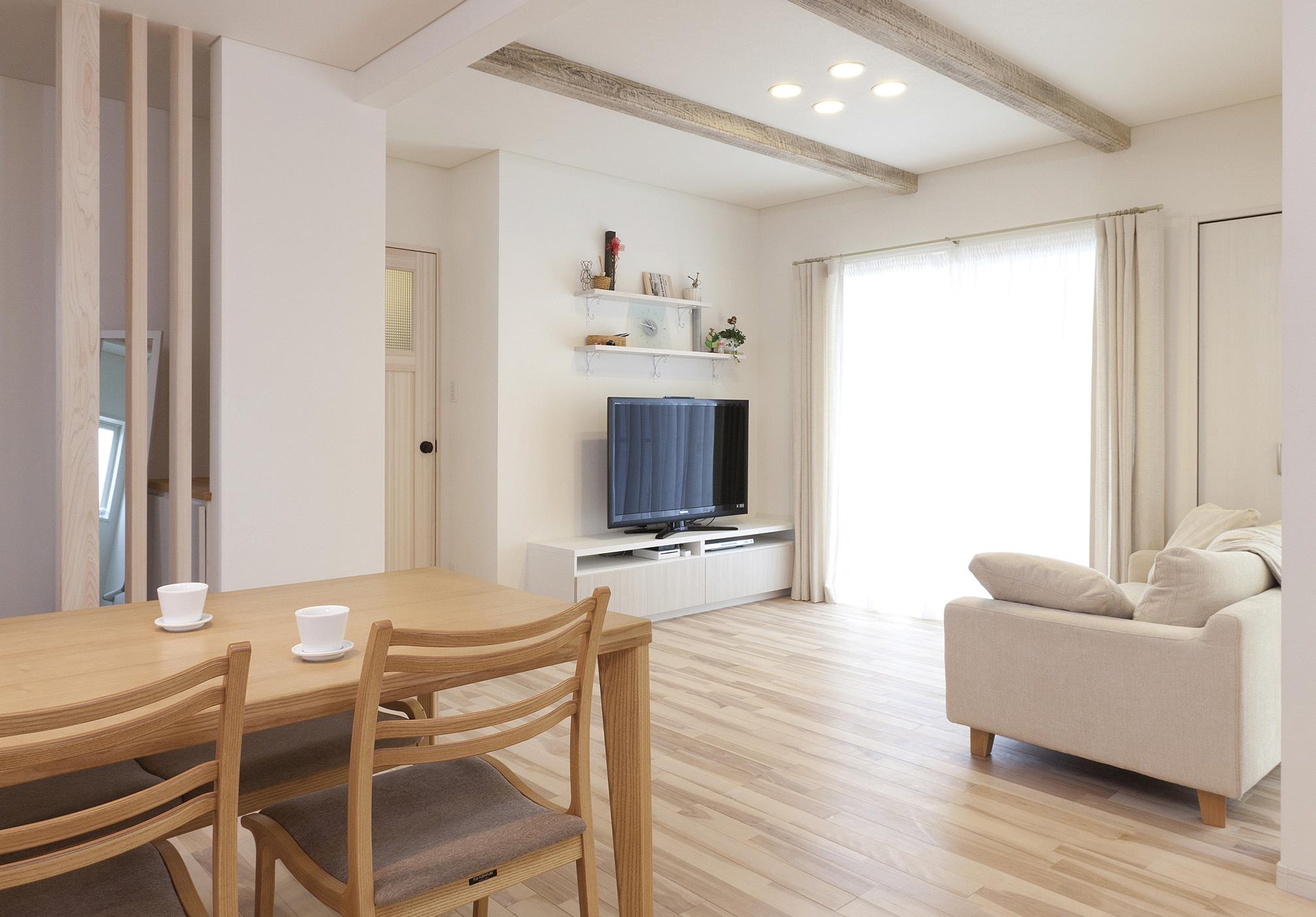 メイプルの無垢材を採用し、白をモチーフにやわらかい光に包まれたリビング・ダイニング。仕切りのないゆったりとした空間は、素朴な味わいを醸し出す天井の化粧梁をアクセントに
