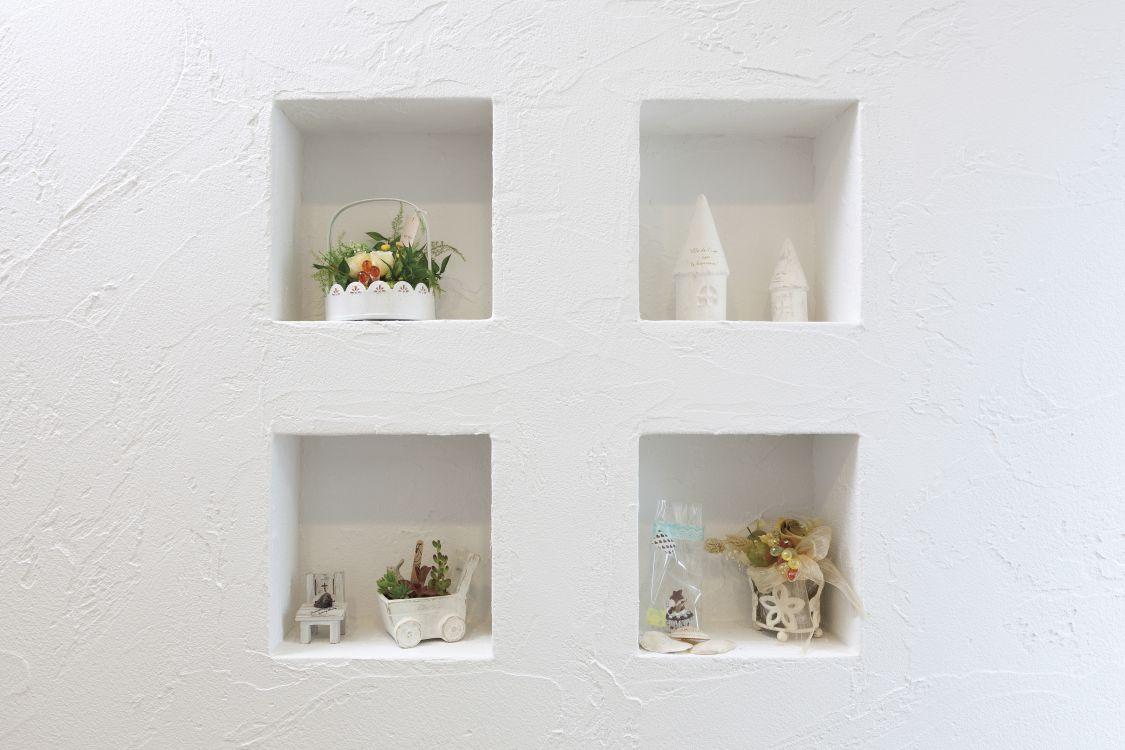 玄関正面の壁には珪藻土を採用。4つのニッチにはお気に入りの雑貨をディスプレイ