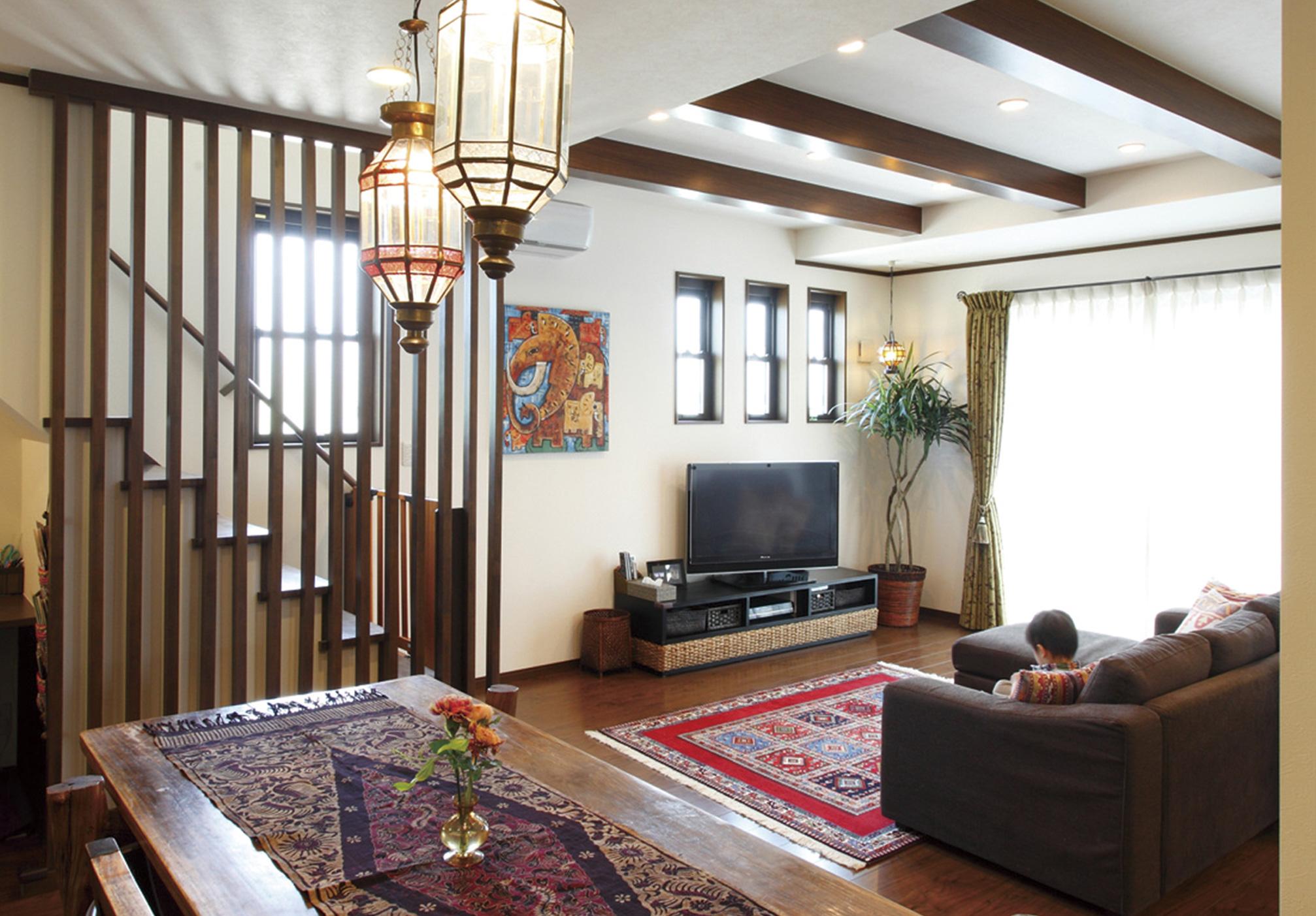 Yさんお気に入りの家具や雑貨、レトロなランプ型の照明などによりアジアンテイストにコーディネートされたリビング・ダイニング。折上天井や階段の格子も空間のアクセントに