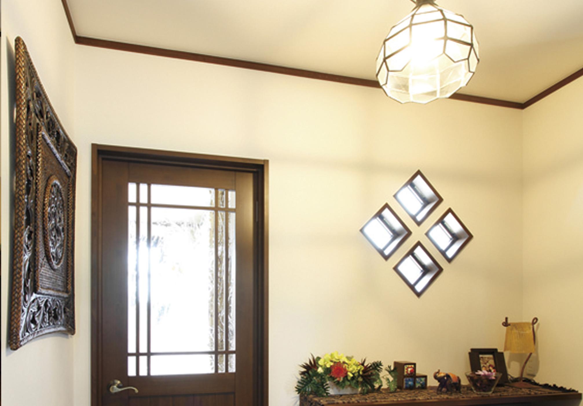 床や扉などはウォールナット色で統一。玄関ホールに組み込まれた菱型のFIX窓もお洒落