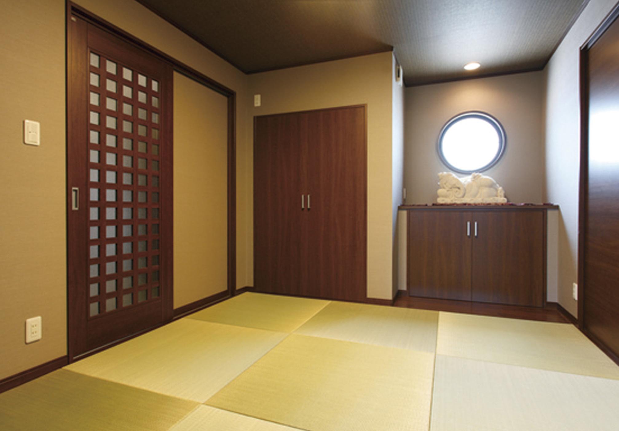 半畳サイズの畳を用い丸窓と飾り棚を備えたモダンな和室。玄関からも直接出入りが可能