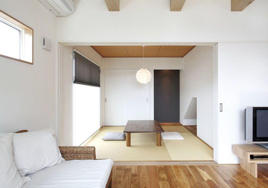 リビングと続き間のモダンな和室。階段下の玄関を有効利用した収納スペースも見える