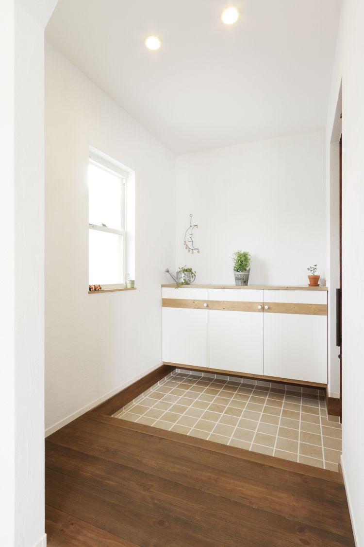 玄関ホールは、木をあしらった玄関収納とタイル敷きにより可愛らしい空間に仕上げた