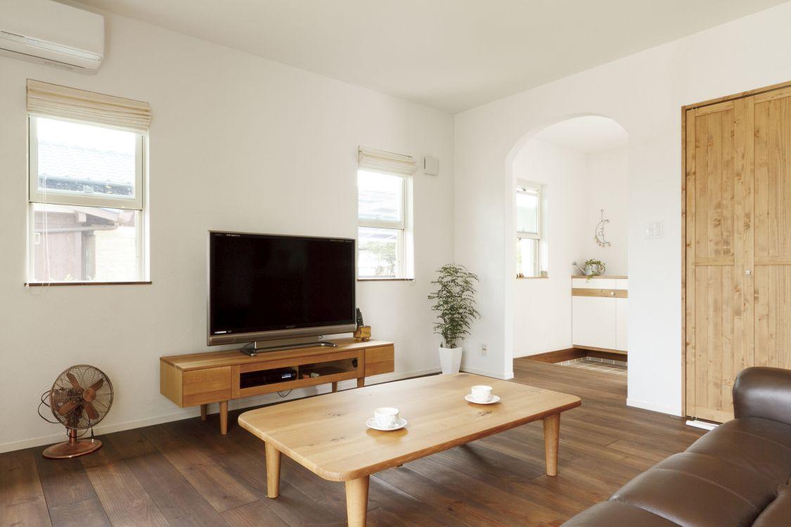 アーチを描く開口部の造作が、自然素材と共にやさしい雰囲気を醸し出しているリビング。Nさんが選んだ家具や無垢の木を使った日興ホームオリジナルの扉が空間に趣を添えている