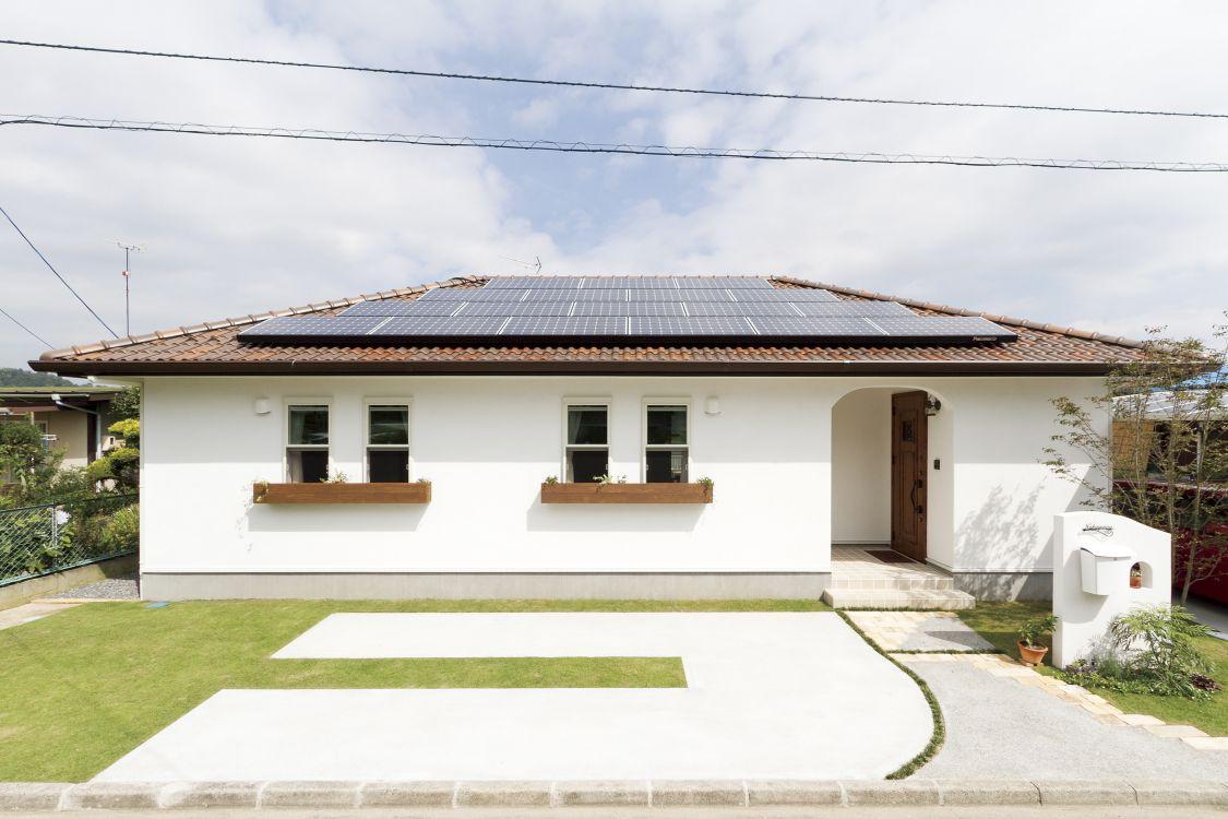 褐色の屋根瓦が印象的な平屋建てのお住まい。屋根には太陽光発電システムを設置